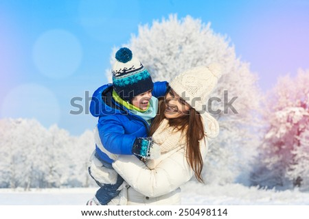 Happy family on a winter walk. Mother and baby boy in the white snowy day, winter vacation - stock photo