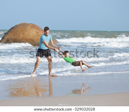 happy family on beach playing, father with son walking sea coast, rocks behind smiling enjoy summer vacation