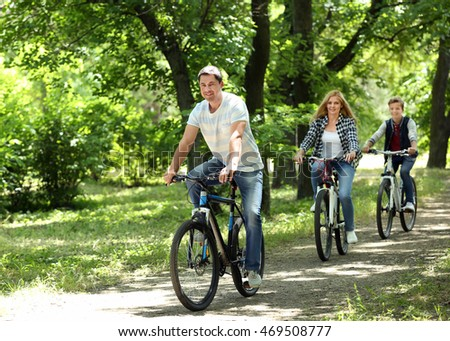 Happy family on bike ride in park