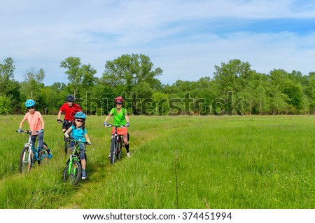 Happy family on bikes, cycling with kids  - stock photo