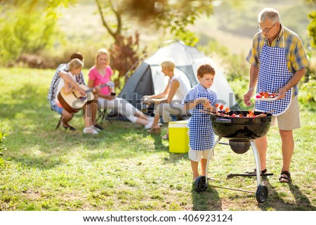 happy family on camping making barbecue - stock photo