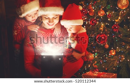 happy family on Christmas Eve. mother and children discover a magical gift at the tree
