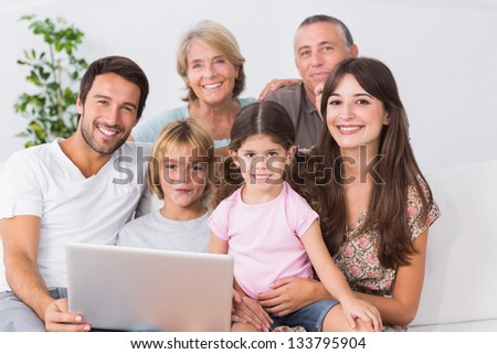 Happy family on couch using laptop in the living room - stock photo