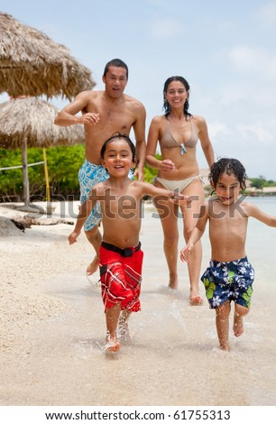 Happy family on holidays playing at the beach
