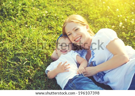 happy family on nature. mom and baby daughter lying are playing and laughing in the green grass - stock photo
