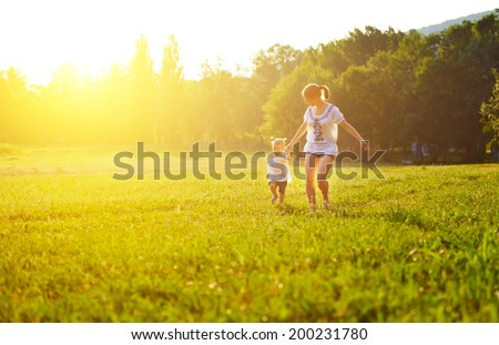 happy family on nature walks in the summer. mother and child run on field - stock photo