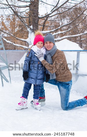 Happy family on skating rink outdoors