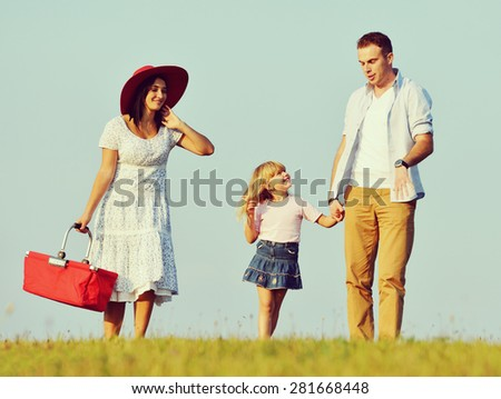 Happy family on summer grass field - stock photo