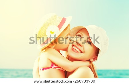 happy family on the beach. baby daughter kissing mother  at sea - stock photo