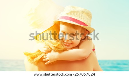 happy family on the beach. baby girl hugging her mother at the sea - stock photo