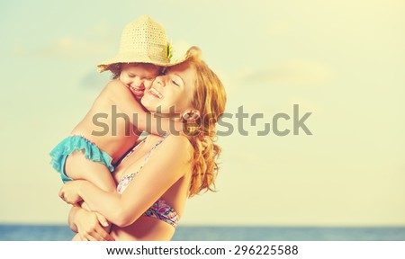 happy family on the beach. mother and baby daughter hug at sea - stock photo