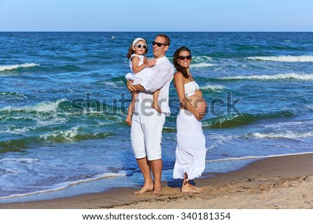Happy family on the beach posing relaxed with pregnant mother woman - stock photo