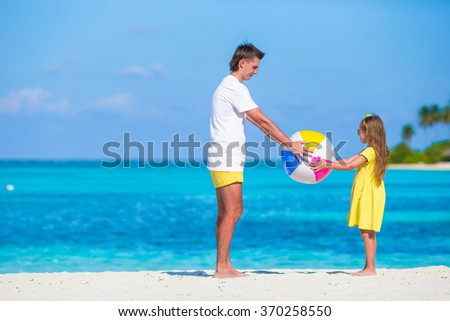 Happy family on the beach with ball having fun together - stock photo