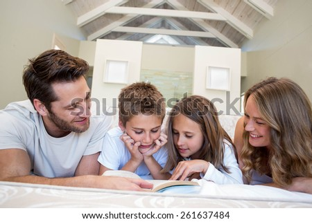 Happy family on the bed reading book at home in bedroom - stock photo