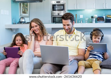 Happy family on the couch together using devices at home in the living room - stock photo