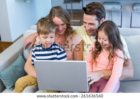 Happy family on the couch together using laptop at home in the living room - stock photo
