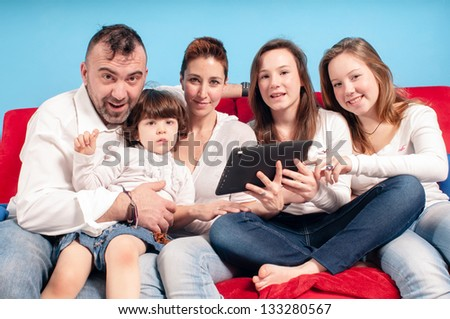 happy family on the couch using tablet in the living room
