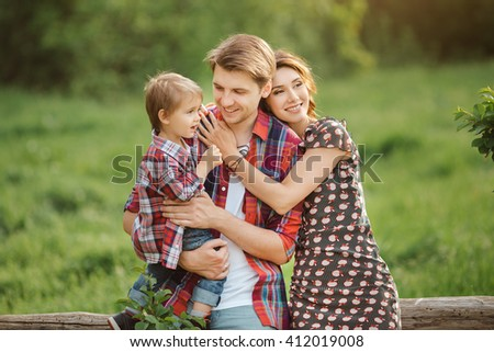 Happy Family on the nature. Mother father and son in casual clothes, sit on a fence, rural look , outdoors - stock photo