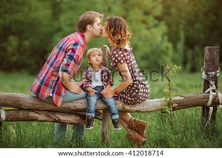 Happy Family on the nature. Mother father kissing and in casual clothes, sit on a fence, rural look , outdoors - stock photo