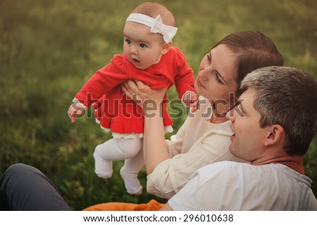 happy family on the walk with baby daughter in red dress in summer park - stock photo