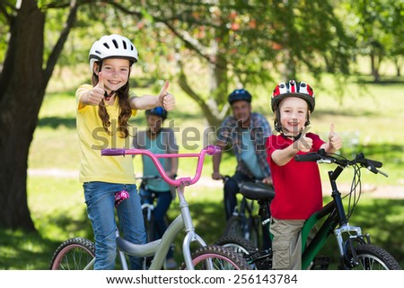 Happy family on their bike at the park with thumbs up on a sunny day - stock photo