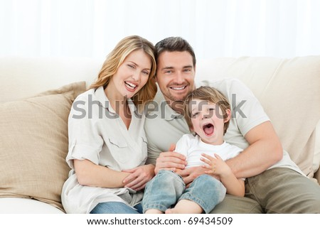 Happy family on their sofa at home - stock photo