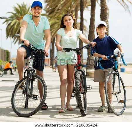 happy family on vacation riding bicycles  and smiling - stock photo