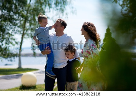 Happy family on walk in summer - stock photo