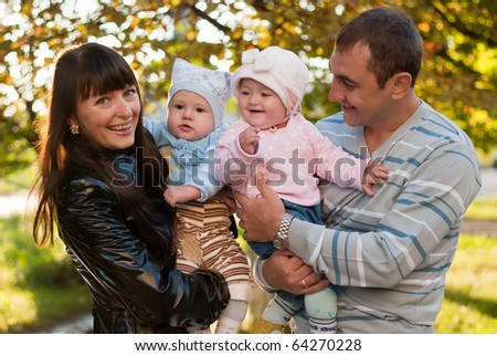 Happy family outdoor - mother, father, daughter and son are smiling - stock photo