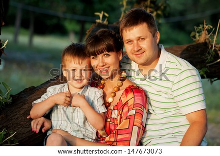 Happy family outdoors. Father, mother and son smiling.