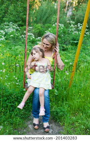 Happy family outdoors  mother and kid, child, daughter smiling playing, swinging