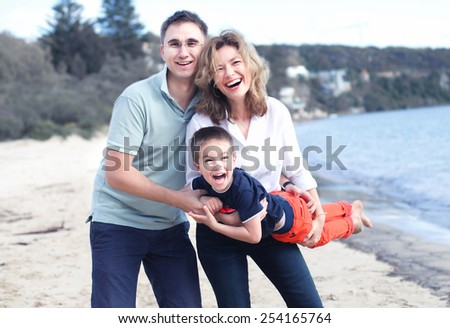 happy family outdoors on a beach smiling - stock photo