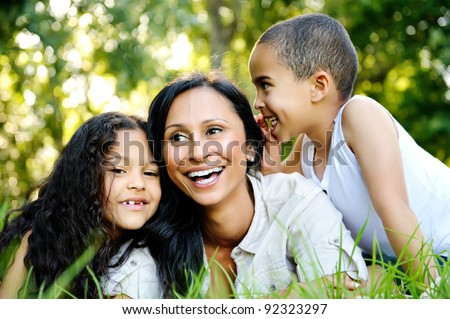 happy family outdoors on the grass in a park. mom and two children smiling - stock photo
