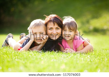 Happy family outdoors on the grass in a park, smiling faces all lying down having fun