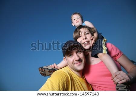 Happy family outdoors over blue sky - stock photo