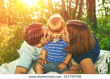 Happy family outdoors. Parents kissing their child. - stock photo