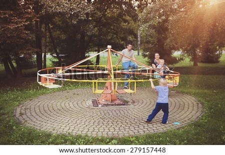 Happy family outside in a park on an old carousel. - stock photo