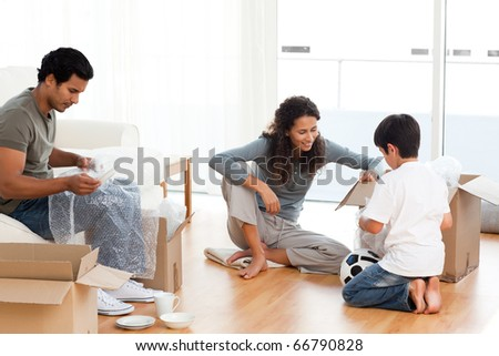 Happy family packing dishes together in their living-room for their removal - stock photo