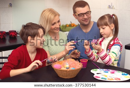 Happy family painting eggs for Easter - stock photo