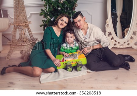 Happy family parents and kid with gifts near the Christmas tree. Christmas, New Year, holiday concept - stock photo