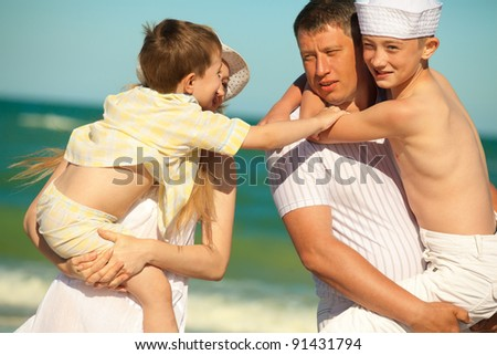 Happy family. Parents holding  sons in theirs arms on beach while on vacation - stock photo