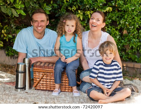 Happy family picnicking in the garden - stock photo