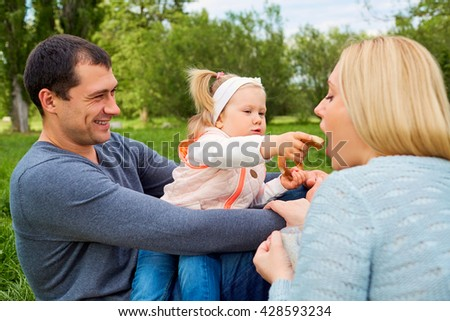 Happy family picnicking in the park. Daughter feeding mother playfully. - stock photo