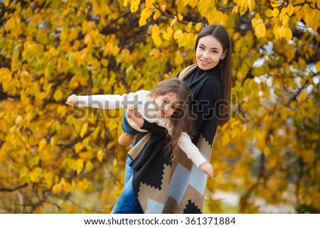 Happy family playing against blurred autumn leaves background. Mother and daughter outdoors. Young mother and her toddler girl have fun - stock photo