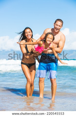 Happy Family Playing and Having Fun on the Beach