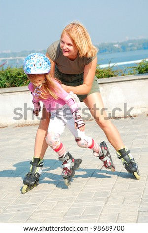 happy family playing and skating  on her in-line rollerblade skates - stock photo