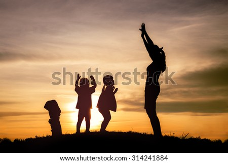 Happy family playing at grass on sunset