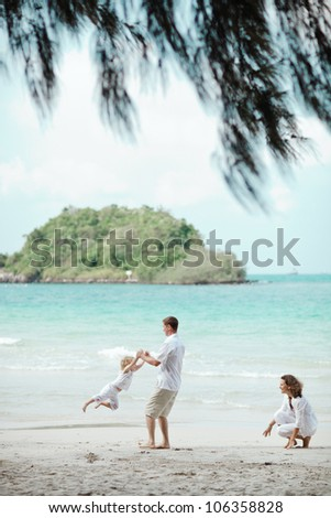 Happy family playing at the beach - stock photo