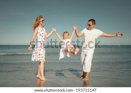 Happy family playing at the beach at the day time