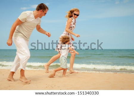 Happy family playing at the beach in the day time - stock photo